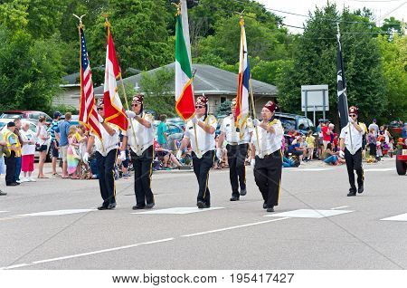 MENDOTA, MN/USA - JULY 8, 2017: Shriners march bearing flags at annual Mendota Days Parade through main street of the historic city. Mendota is one of the first permanent settlements in Minnesota.