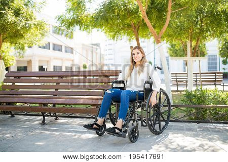 Optimistic Woman Sitting On A Wheelchair