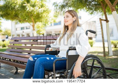 Woman In Wheelchair Listening To Music