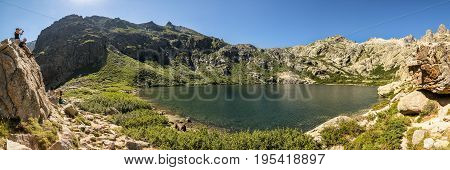 LAC DE MELO NEAR CORTE CORSICA - JULY 2017. Holidaymakers enjoy the view at Lac de Melo on a sunny July day