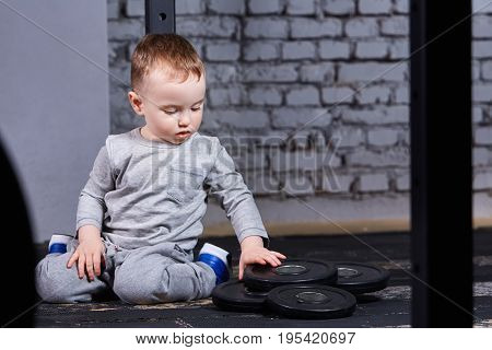 Little cute boy in sportwear sitting on the floor at the gym and looking on the barbell against brick wall. Sporty child in the grey sportwear and blue sportive shoes. Child rearing in the healthy lifestyle.