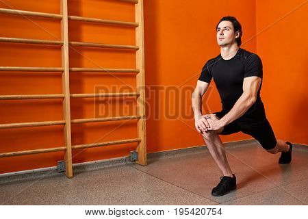 Young sportsman standing against bright orange wall and stretching legs before gym workout. Athlete man in the black sportwear, t-shirt, shorts and sporty shoes. Horizontal photo. Healthy lifestyle.