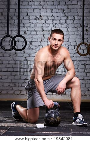 Young sportsman crouching on a one leg and holding kettlebell against brick wall in the cross fit gym. Athletic man in the shorts and sporty shoes. Vertical photo. Healthy lifestyle.