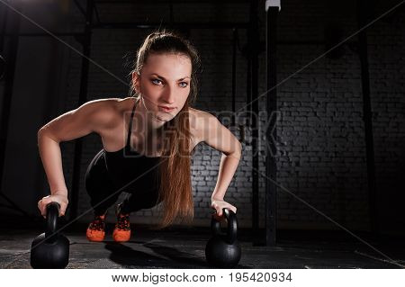 Young athlete woman in the black sportwear doing push ups on two kettlebells against brick wall in the gym. Sporty woman in the t-shirt, leggings and orange sporty shoes. Close-up photo. Healthy lifestyle.