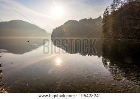The Lake Alpsee On A Foggy Day With The Sun Coming Through Near The Neuschwanstein Castle