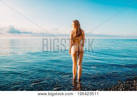 Beautiful woman with perfect body in swimwear standing up on the beach, wearing stylish bikini