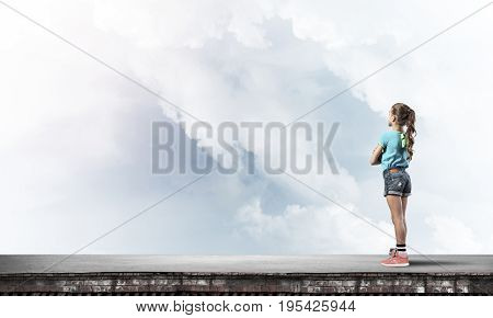 Cute kid girl standing on building roof with hands crossed on chest