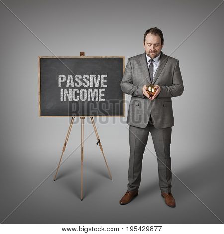 Passive income text on  blackboard with businessman and golden egg