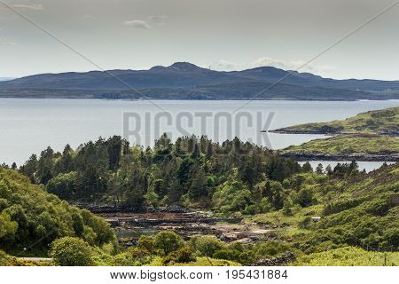 Assynt Peninsula Scotland - June 7 2012: Green rough hilly forested shoreline of Atlantic Ocean inlet near Loch An Arbhair with mountains on horizon.