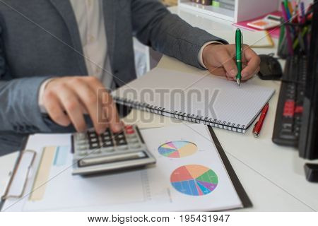close up businessman hand using pen for writing data information on paperwork concept. A businessman doing some paperwork using his calculator