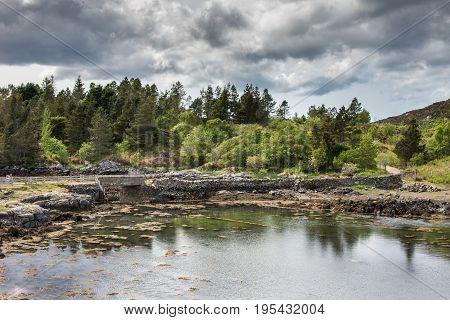 Assynt Peninsula Scotland - June 7 2012: Short stone bridge over creek landing into Atlantic Ocean inlet South of Loch An Arbhair under heavy dark sky. Forested green hillsocean waters road.