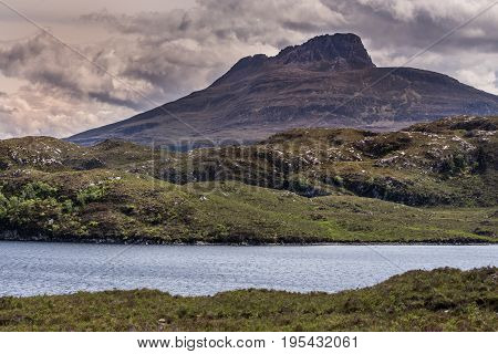 Assynt Peninsula Scotland - June 7 2012: Brown mountain peak under heavy brownish skies fronted by green wild rough slopes east of Loch Buine Moire. Lake waters in front.