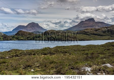 Assynt Peninsula Scotland - June 7 2012: Three brown mountain peaks under heavy brownish skies fronted by green wild rough slopes east of Loch Buine Moire. Lake waters in front.