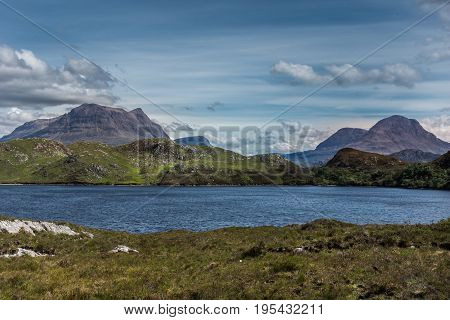 Assynt Peninsula Scotland - June 7 2012: multiple brown mountain peaks under blue skies with gray clouds fronted by green wild rough slopes east of Loch Buine Moire. Lake waters in front.