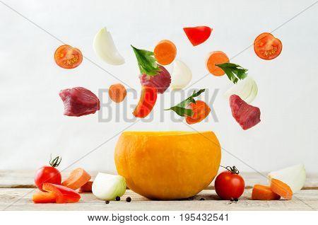 Pumpkin and flying ingredients for cook beef stew in pumpkin