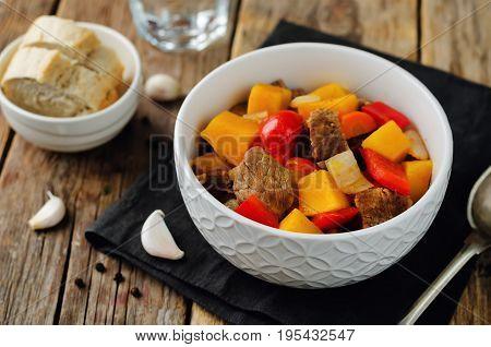 Pumpkin beef stew on a wood background