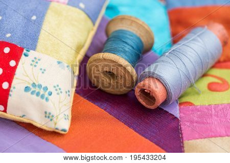 patchwork, quilting, sewing, tailoring and fashion concept - closeup on beautiful colorful stitched cushion and spools of blue thread at background of blue, lilac and red flaps of fabric.