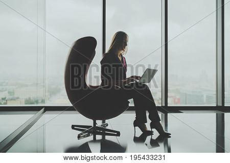 Silhouette of charming businesswoman sitting alone near panoramic office window and working on her laptop attractive female boss using her notebook while sitting on curved armchair in office hall