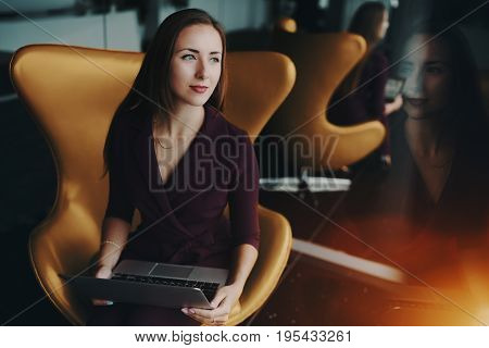 Portrait of charming adult caucasian businesswoman sitting on yellow elegant armchair with modern laptop next to mirror in luxury office with multiple reflections and wistfully looking aside