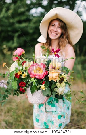 wedding, floral design, beauty, country life concept - charming laughing woman in straw hat and summer dress with bouquet of grand beautiful peonies, soft yellow avalanches and bright red carnations