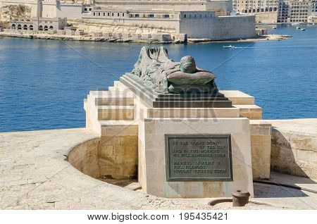 View of the War sculpture by Michael Sandle from the Siege Bell War Memorial or Malta Siege Memorial at the entrance to the Grand Harbour in Valletta toward Fort St.Angelo and Birgu an old fortified city in the South Eastern Region of Malta.