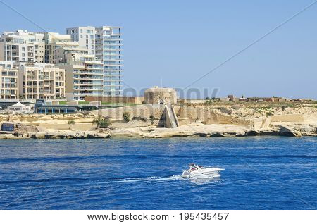 Tigne Point with Fort Tigne with its circular keep built by the Order of Saint John one of the oldest polygonal forts in the world and modern residential buildings in Sliema as seen from Valletta Malta
