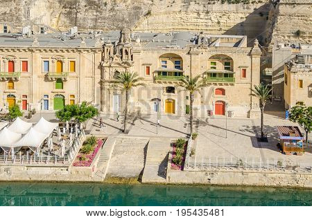 Valletta, Malta - June 4 2017: Part of Valletta Waterfront also known as Pinto Wharf or Pinto Stores a baroque wharf in Floriana with its colourful windows the old seawall palm trees and tourist information office.