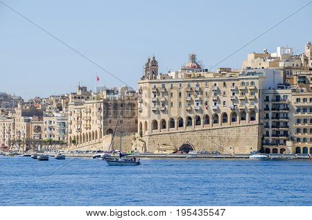 Senglea Malta - June 4 2017: Senglea waterfront as seen from the Grand Harbour its modern part with buildings adapted to the old maltese architectural style maltese flags on balconies and sailing boats