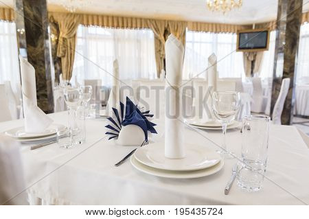 Festive table setting in classic style in a white restaurant interior, setout, layout. holiday table decor concept. Expectation of guests.