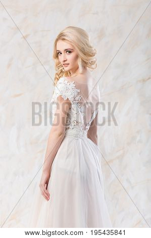 fashionable wedding dress, beautiful blonde model, bride hairstyle and makeup concept - elegant young woman in luxury white gown indoors on light background, pretty female posing in the studio