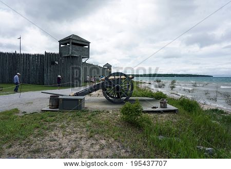 MACKINAW CITY, MICHIGAN / UNITED STATES - JUNE 18, 2017: A cannon is aimed at the Straits of Mackinac, near the north entrance of Fort Michilimackinac, at the Colonial Michilimackinac State Park.