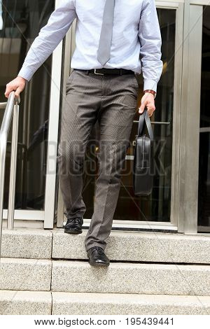 Businessman walking out from the office after working day and holding a leather briefcase in his hand