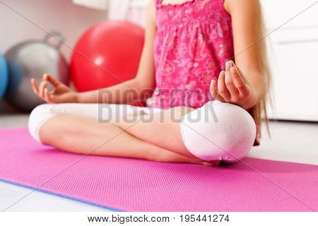 Young girl meditating or relaxing in the lotus yoga pose - sitting on the floor at home or at the gym