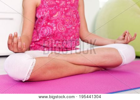 Young girl relaxing in the lotus yoga pose at home - closeup