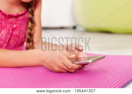 Young girl checking her phone lying on the floor at home - closeup on hands, copyspace