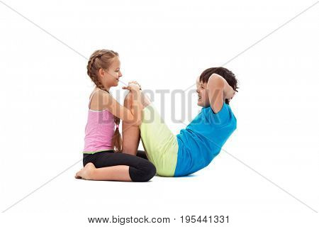 Young kids doing abs exercises together - helping each other, isolated