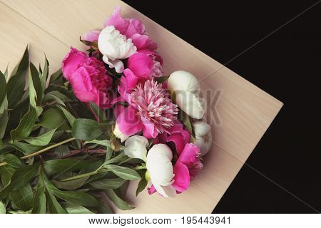 Beautiful bouquet with fragrant peonies on light wooden table