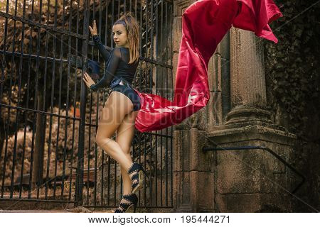 Girl posing on the streets of the Spanish city of Orense, Galicia. Brunette in tight black dress and big red cloth in the wind