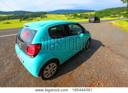 SUMAVA CZECH REPUBLIC - JULY 14, 2017: Traffic on road in National Park Sumava. Many tourists going to holidays in countryside. On foreground is small car Citroen C1 with The PureTech 82 petrol engine