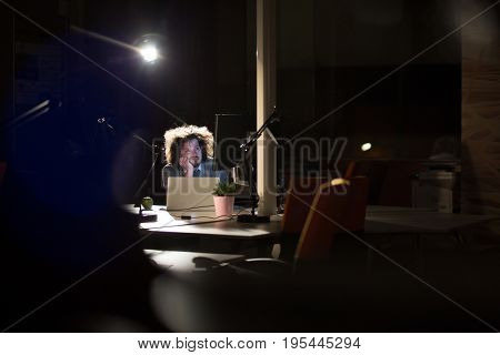 A time for relax. Young tired casual businessman relaxing at the desk in his night office