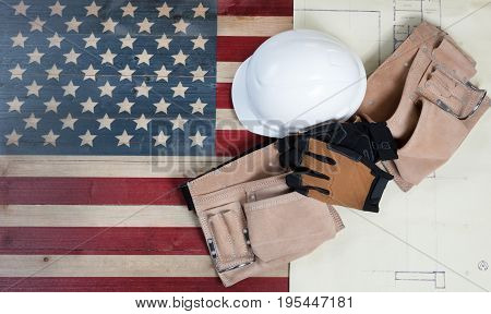 Labor Day background with USA rustic wooden flag drawing blue prints and used industrial tools plus utility belt