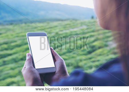Mockup image of a woman holding and using white smart phone with blank screen at outdoor and green nature background