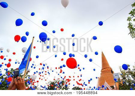 Colorful balloons floating in the air above Phra Pathommachedi.