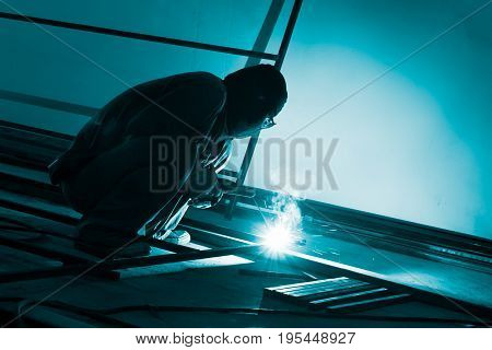 worker making sparks from welding steel in dark room