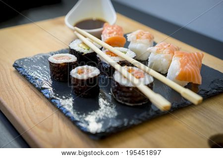 Gourmet, Sushi on a wooden table on black slate plate with soy sauce and chopsticks