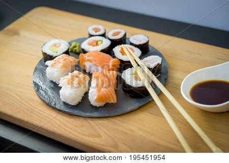 Sushi with wasabi on a wooden table on black slate plate with soy sauce and chopsticks