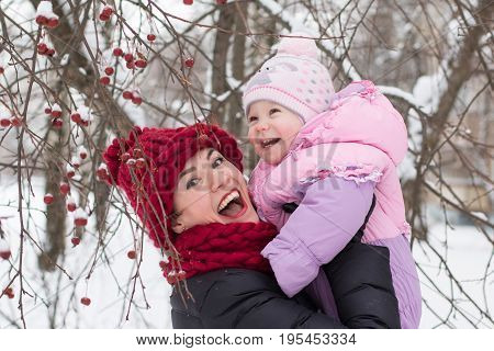 Beautiful mom and nice baby outdor in a winter day