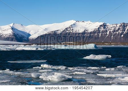 Iceland winter lake with snow coverd mountian and clear blue sky background natural winter landscape