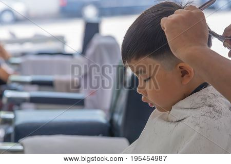 image of young asia boy at barber shop .