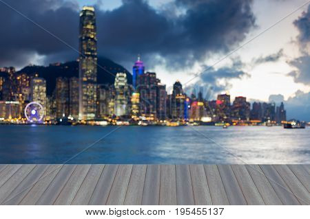 Opening wooden floor Twilight blurred bokeh light office building Hong Kong city seafront abstract background